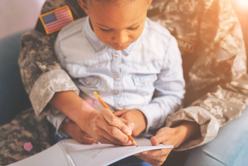Military mother with a child on lap making notes
